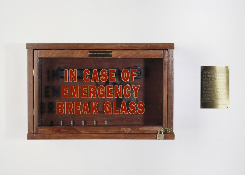 1990; wood, gun, bullets, text on signs; 12 x 24 x 8 inches